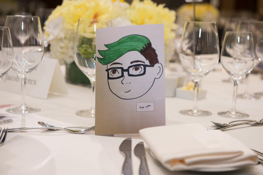 artwork with stemware and flowers on guest table at gala