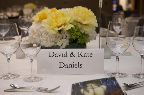 table placement sign with stemware and flowers on guest table at gala