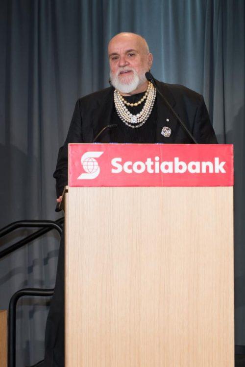 man speaking at gala standing behind a podium