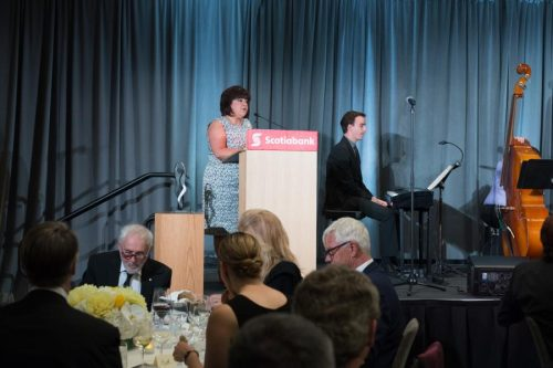 executive director speaking at the podium at gala