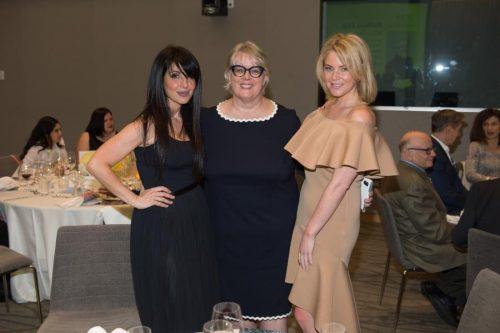 three women posing for camera at gala