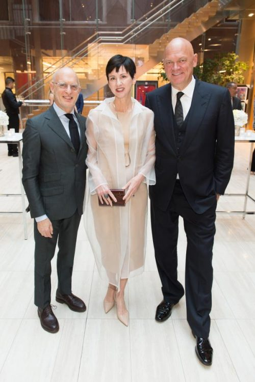 two men and a woman pose at gala