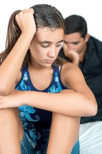 Troubled and sad teenage girl with her worried father