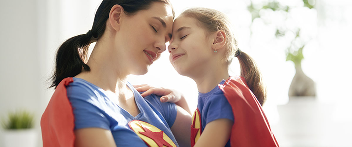 mother and daughter dressed in superhero costumes embracing