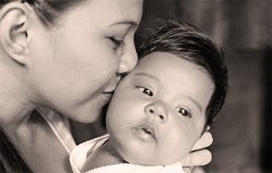 mother kissing infant on the cheek