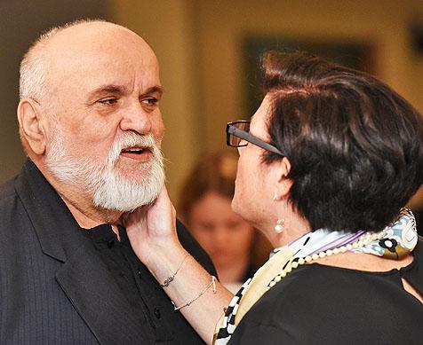 woman touches cheek of man at gala