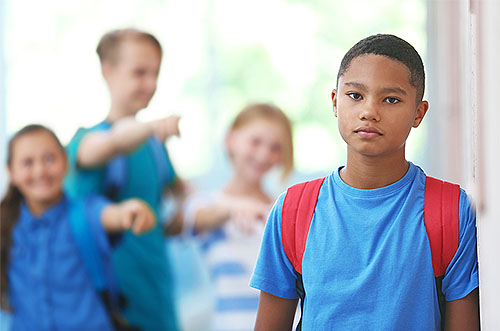 young man feeling sad with mean kids pointing at him